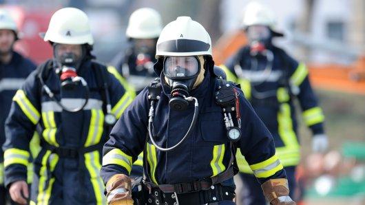 Feuerwehrleute mit Gasmasken sind wegen einer bei Baggerarbeiten beschädigten Gasleitung im Einsatz (Symbolbild).