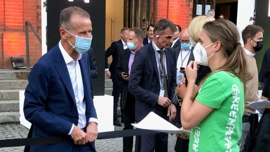 Marion Tiemann, Verkehrsexpertin von Greenpeace, übergibt VW-Chef Herbert Diess etwas.