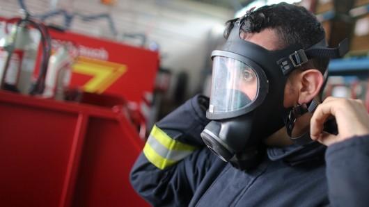 Ein Feuerwehrmann legt seine Schutzkleidung und Atemschutzmaske an. (Symbolbild)
