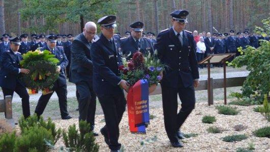 Feuerwehrleute legen Kränze für ihre Kameraden nieder.