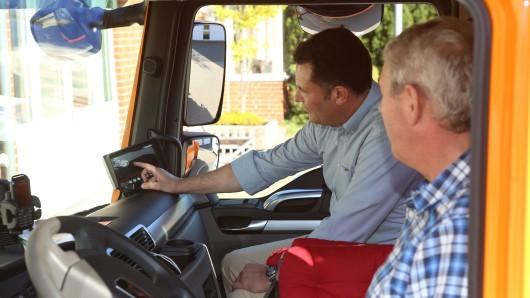 Bürgermeister Matthias Nerlich und Bauhofmitarbeiter Alexander Kunstmann erklären die Vorteile des Abbiegeassistenten. Auf dem Monitor erkennt der Fahrer einen Mann im toten Winkel.