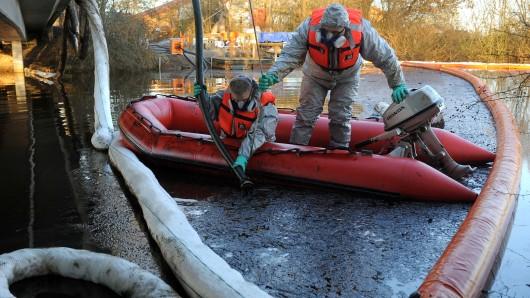Experten saugen  vom Schlauchboot aus einen Ölfilm von der Wasseroberfläche eines Teichs. (Archivbild)