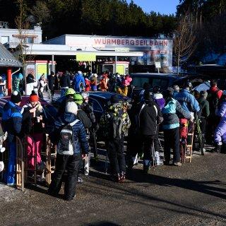 Wintersportler stehen an der Wurmbergseilbahn in einer Warteschlange an.