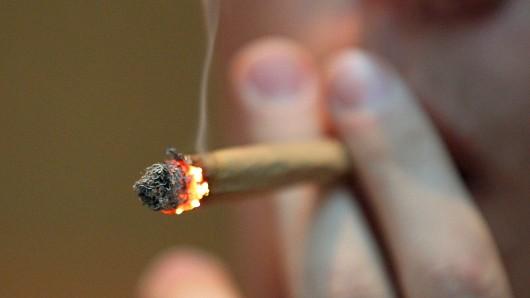 """ARCHIV- ILLUSTRATION- Ein Mann raucht am 18.04.2012 im Coffee Shop """"Easy Going"""" in Maastricht einen Joint mit Marihuana. Frankfurts Gesundheitsdezernent Stefan Majer (Grüne) stellt eine Drogenstudie vor, in der es unter anderem um Veränderungen beim Cannabis-Konsum Jugendlicher geht. (zu dpa """"Drogenstudie wird vorgestellt - Veränderungen beim Cannabis-Konsum"""" vom 25.10.2017) Foto: Oliver Berg/dpa +++(c) dpa - Bildfunk+++"""