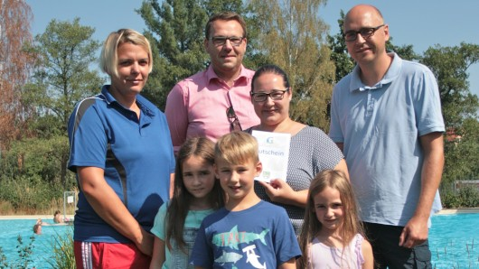 Können sich über einen Gutschein freuen: Tina Langeleist, Frank Krieger und ihre Kinder Lillia, Kilian und Juna. Schwimmmeisterin Mandy Rügenhagen und Samtgemeinde Bürgermeister Gero Janze freuen sich mit.