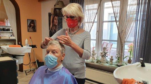 Friseurin Klaudia Rekers mit einer Kundin. Nach der Zwangspause darf sie wieder Haare schneiden – doch vieles ist anders als zuvor.