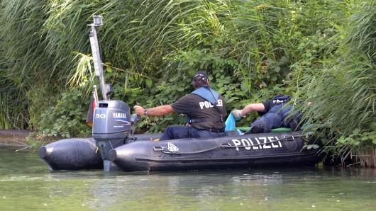 Zwei Polizeibeamte ziehen am 3. August 2015 eine Plastiktüte am Ufer des Mittellandkanal in Hannover aus dem Wasser. Bei Reinigungsarbeiten sind im Mittellandkanal in Hannover mehrere Teile einer männlichen Leiche in Plastiktüten gefunden worden. (Archivbild)