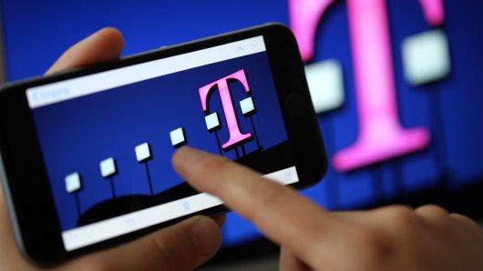 Ein Frau tippt auf ihr Smartphone, auf dem ein Telekom-Logo zu sehen ist. Bei dem Mobilfunkanbieter sollen es eine Datenpanne gegeben haben.