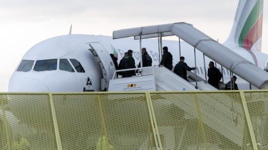 Abgelehnte Asylbewerber steigen bei einer Sammelabschiebung in ein Flugzeug (Archivbild).