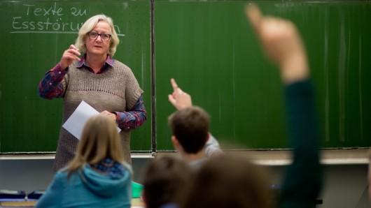 Eine Lehrerin unterrichtet vor einer Schulklasse.