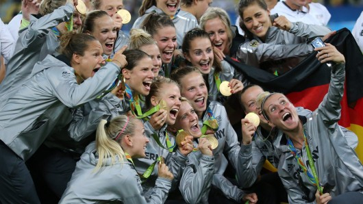 Die Fussball-Frauen halten stolz ihre Goldmedaillen hoch zum Selfie.
