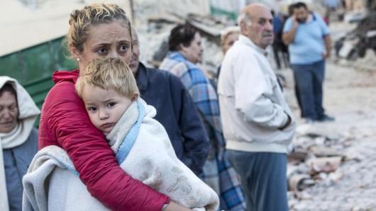 Eine Mutter hält ihren Sohn in den Armen. In ihrer Heimatstadt Amatrice ist nach dem Erdbeben nichts mehr wie zuvor.