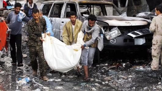 Helfer tragen ein Opfer des Bombardements einer Trauerhalle aus den Trümmern.