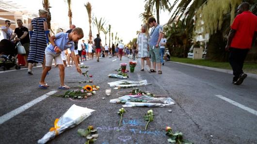 Ein Kind legt Blumen auf der Straße in Nizza nieder, in der ein Lkw bei einem Terroranschlag in eine Menschenmenge gerast war.