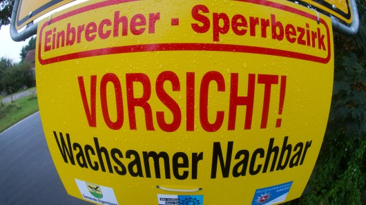 Ein Schild mit der AUfschrift Vorsicht! Wachsamer Nachbar (Symbolbild)