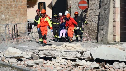 Retter tragen eine verletzte Frau durch die teilweise zerstörte Stadt Norcia.