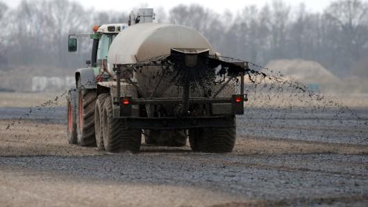 Mit einem Traktor wird ein Güllewagen über ein Feld bei Jacobidrebber (Niedersachsen) gezogen. Das Bundesland ist bei der DEbatte um zu hohe Nitratwerte besonders im Fokus. (Archivbild)