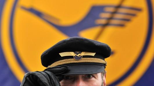 Mit seiner Uniformmütze auf dem Kopf steht ein Pilot der Lufthansa vor seiner Maschine (Symbolbild).