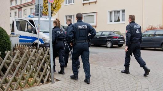 Polizisten gehen am 21. November über eine Straßenkreuzung in Hameln. Hier hatte am Vorabend ein Mann eine junge Frau mit einem Seil an die Anhängerkupplung eines Autos gebunden und rund 250 Meter weit durch Hameln geschleift.