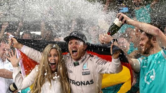 Champagnerdusche nach dem Sieg. Der frischgebackene Formel I-Weltmeister Nico Rosberg und seine Frau Vivian feiern ausgelassen seinen ersten Titel.