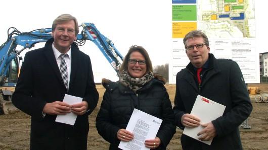 Rüdiger Warnke, Maren Sommer-Frohms und Heinz-Georg Leuer stehen vor dem neuen Bauschild am Alsterplatz.