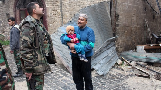 Ein Vater mit seinem Kind in Aleppo, daneben steht ein syrischer Soldat. (Archivbild)