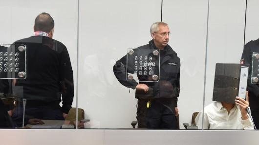 Die beiden Angeklagten Ebrahim H. B. (l.) und Ayoub B. (r., verdeckt von einem Aktenordner) sitzen zu Beginn der Verhandlung am 3. August 2015 in einem mit Sicherheitsglas abgetrennten Raum im Gerichtssaal des Oberlandesgerichts in Celle (Niedersachsen). (Archivbild) Das Gericht hat nun entschieden, den Rest der Haftstrafe von Ebrahim H. B. auf Bewährung auszusetzen.