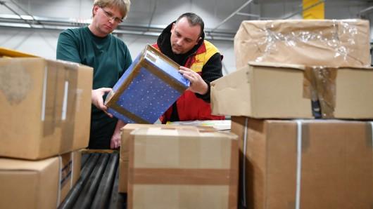 Mitarbeiter des Zolls und der Deutschen Post DHL nehmen  in Speyer in der Zollabfertigungsstelle des Paketzentrums der Deutschen Post Pakete in die Hand und kontrollieren sie.