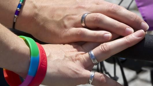 Zwei miteinander verheiratete Frauen halten auf dem Straßenfest zum Christopher Street Day Händchen.