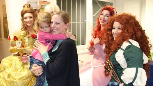 Eine kleine Beschenkte ist schon ganz müde. Um sie herum die Märchen-Prinzessinnen aus Die Eiskönigin.
