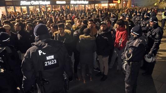 Polizisten umringen am 31. Dezember 2016 vor dem Hauptbahnhof in Köln eine Gruppe südländisch aussehender Männer.