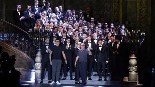 Die Designer Stefano Gabbana (erste Reihe, l) und Domenico Dolce (erste Reihe, M) stehen nach der Präsentation ihrer Kollektion mit ihren Models auf der Bühne.