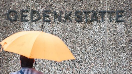 Ein Besucher mit Regenschirm steht vor dem Schriftzug Gedenkstätte auf dem ehemaligen Lagergelände des Konzentrationslagers in Bergen-Belsen.