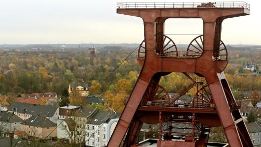 Hinter dem Förderturm von Zeche Zollverein haben sich die Baumkronen der Stadtbäume der Essener Wohnviertel am in Essen herbstlich gefärbt. Die Stadt Essen stellt ist zur Grünen Hauptstadt Europas gekürt worden.