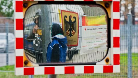 Flüchtlinge stehen am 7. Dezember 2015 neben einem Schild vom Bundesamt für Migration und Flüchtlinge an der Landesaufnahmebehörde Niedersachsen in Braunschweig (Niedersachsen) und spiegeln sich dabei einem Spiegel für Autofahrer. (Archivbild)