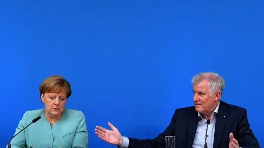 Der bayerische Ministerpräsident Horst Seehofer (CSU) sitzt bei einer Pressekonferenz neben Bundeskanzlerin Angela Merkel (CDU).