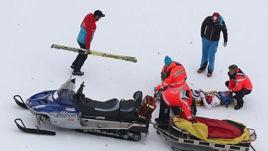 Der österreichische Skispringer Gregor Schlierenzauer wird nach seinem schweren Sturz der Qualifikation ärztlich versorgt und auf einer Trage aus dem Stadion gefahren.