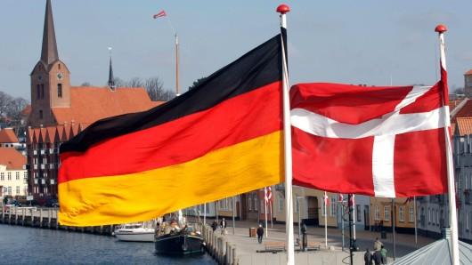 Die Flaggen von Dänemark (r.) und Deutschland wehen nebeneinander (Symbolbild).