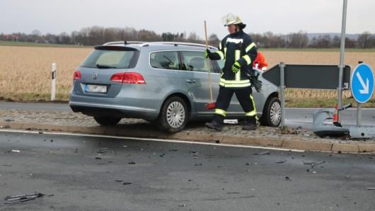 Ein weiteres Fahrzeug steht demoliert auf einer Verkehrsinsel auf der Kreuzung. Die Feuerwehr räumt Trümmer beiseite.