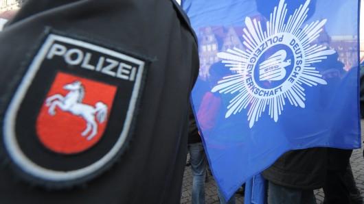 Ein niedersächsischer Polizist mit einer Fahne der Polizeigewerkschaft (Archivbild).