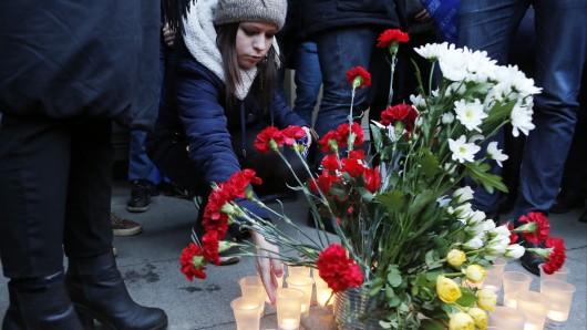 Passanten stellen zum Zeichen ihrer Trauer und ihres Mitfühlens mit den Opfern Blumen und Kerzen vor dem Eingang zu jener U-Bahn-Station auf, in der der Zug nach dem Attentat zum Halten gekommen ist.