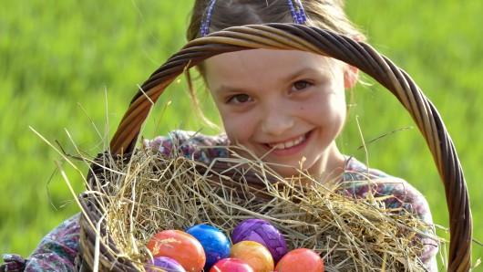 Ein kleines Mädchen hält einen Korb mit Ostereiern.