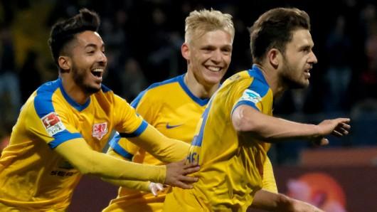 Braunschweigs Ken Reichel (r) bejubelt seinen Treffer zum 1:0 gegen Dynamo Dresden mit Salim Khelifi (l) und Saulo Decarli.