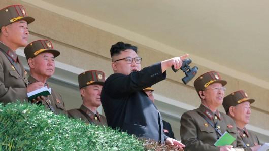 Der nordkoreanische Staatschef Kim Jong Un inmitten von Offizieren.