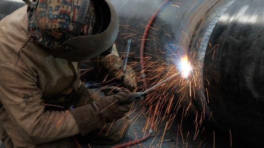 Ein Metallarbeiter schweißt an einer Stahlröhre (Symbolbild).