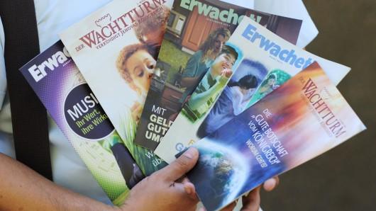 Ein Mitglied der Zeugen Jehovas hält Ausgaben des Wachtturm und Erwachet.