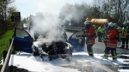 Die Feuerwehrmänner löschen das Auto.