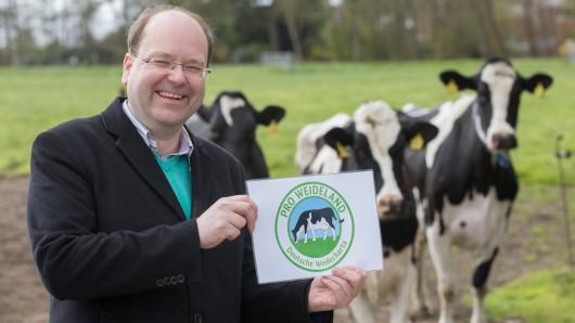 Niedersachsens Landwirtschaftsminister Christian Meyer (Grüne) präsentiert anlässlich des ersten Weideaustriebs auf dem Milchviehhof Hanken das Gütesiegel Pro Weideland.