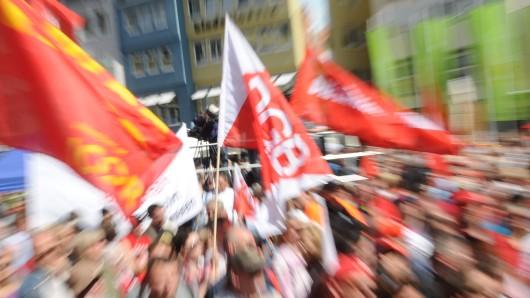 Fahnen des DGB wehen bei einer Kundgebung des DGB am ersten Mai (Archivbild)