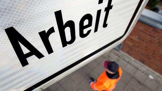 Ein Arbeiter geht unter einem Schild mit Arbeit hindurch. Die Beschäftigungszahlen in Deutschland liegen auf neuem Rekordniveau (Symbolbild).